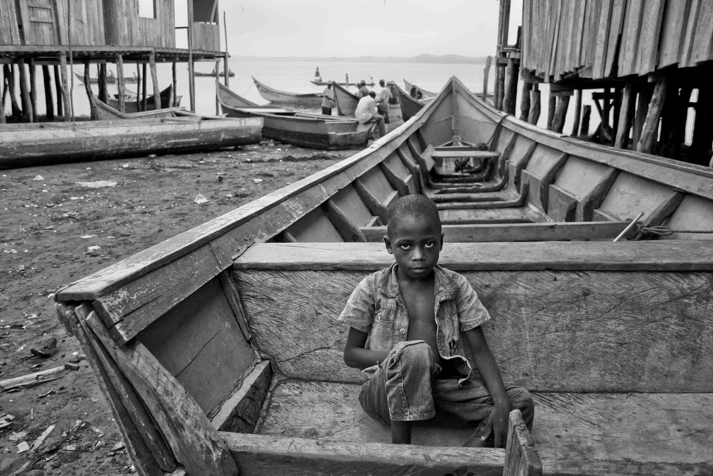 A child sitting on a boat looks at the camera. Pampanal de Bolívar, Ecuador. 2010.