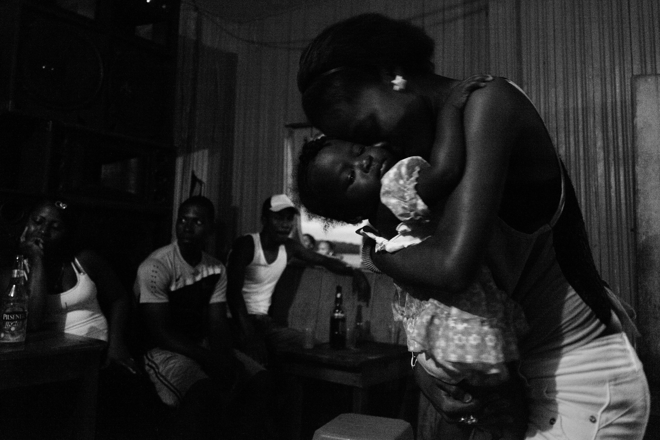 A woman dances with a baby at a bar in the community of Tambillo. In the communities, Sundays are mostly reserved for drinking and partying. Tambillo, Ecuador. 2014.