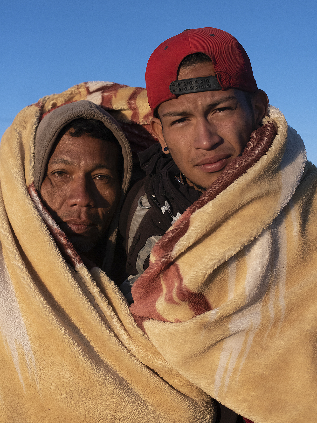 Franklin Aguilar and his nephew Sebastian Aguilar cover themselves with a blanket in the Berlin highlands. Franklin was a physical education teacher in Valencia, Venezuela. He is from a town where it is very hard to find food and basic items. He would have to travel to other towns to buy food but was robbed repeatedly by thieves that pray on people traveling to buy food.