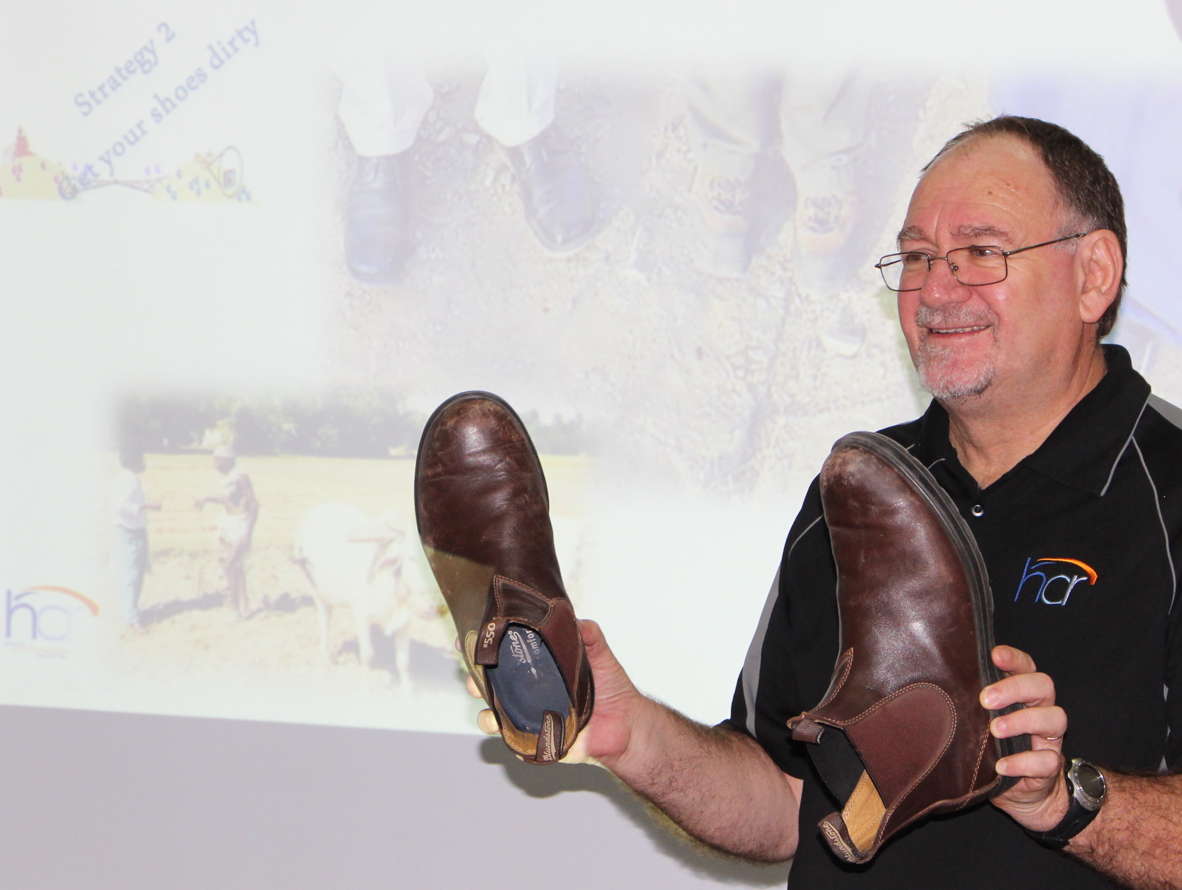 "Dr. Ross James shows workshop participants in Pakistan his shoes, saying,  ""If you want to change communities you need to get your shoes dirty."""