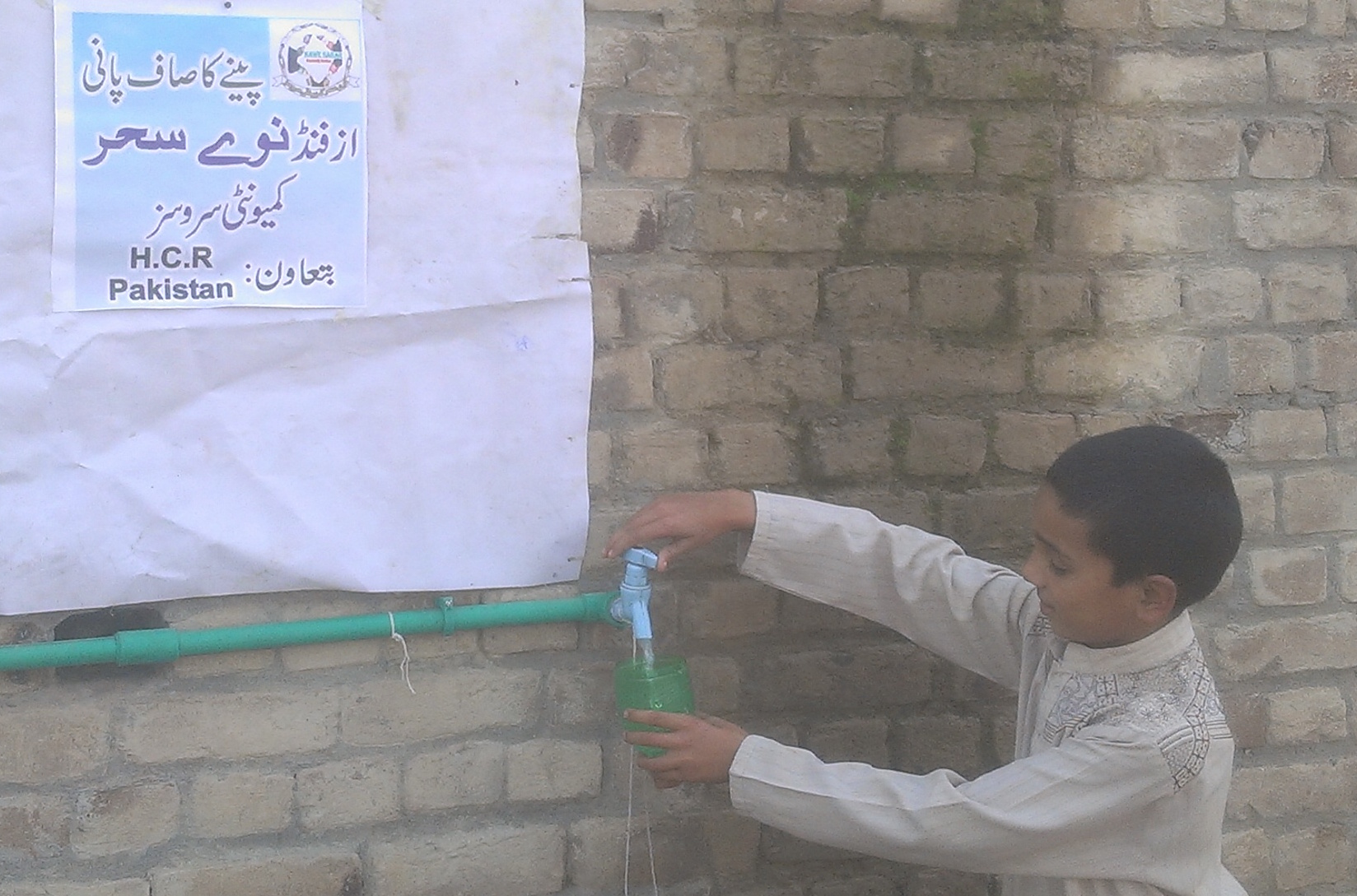 Schoolboy tries the clean drinking water from the new well in his village, KPK province, Pakistan