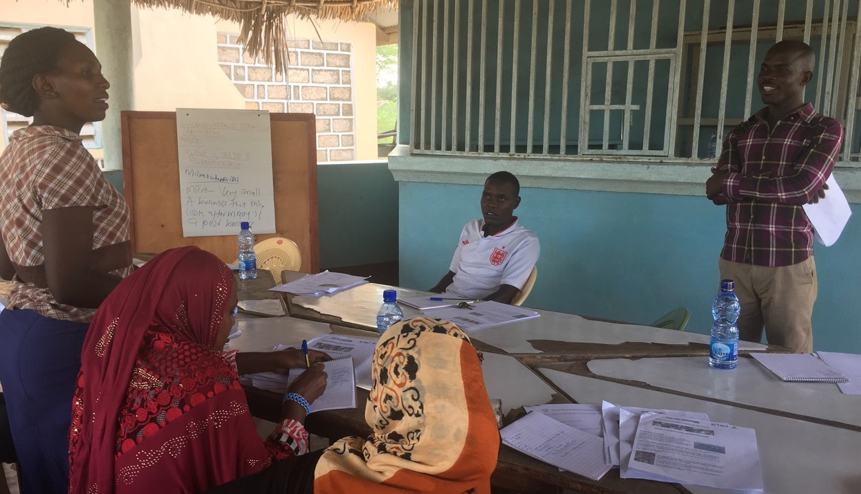Philip Amara (right) interacts with participants during a workshop to train budding entrepreneurs in Tana River County