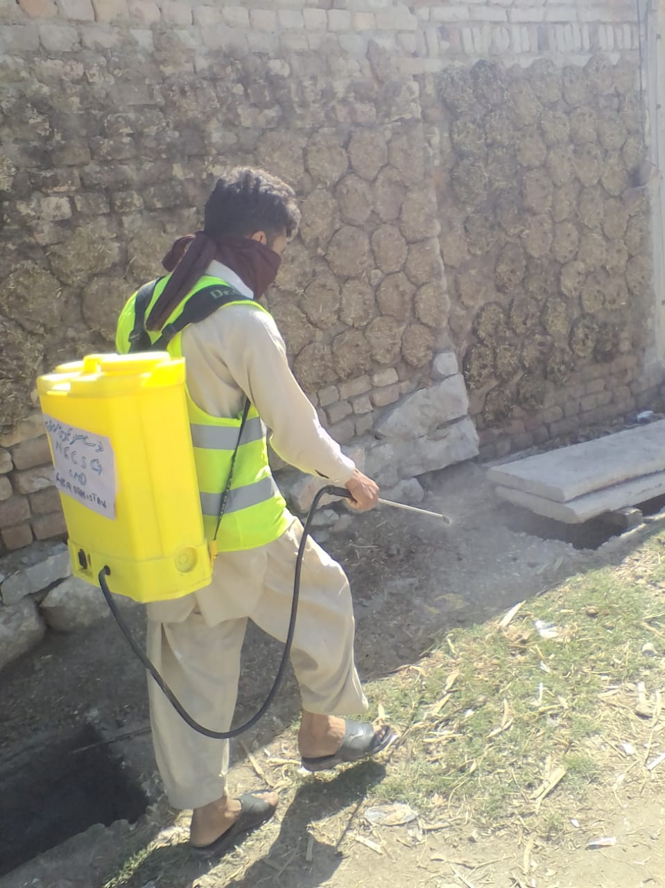 NSCSG spraying drains to prevent mosquitoes from breeding and disease from spreading
