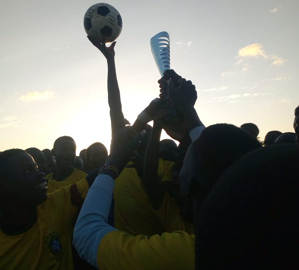 Members of the Rapid Deployment Unit lift the trophy for the  Amani Ni Mimi  community football match