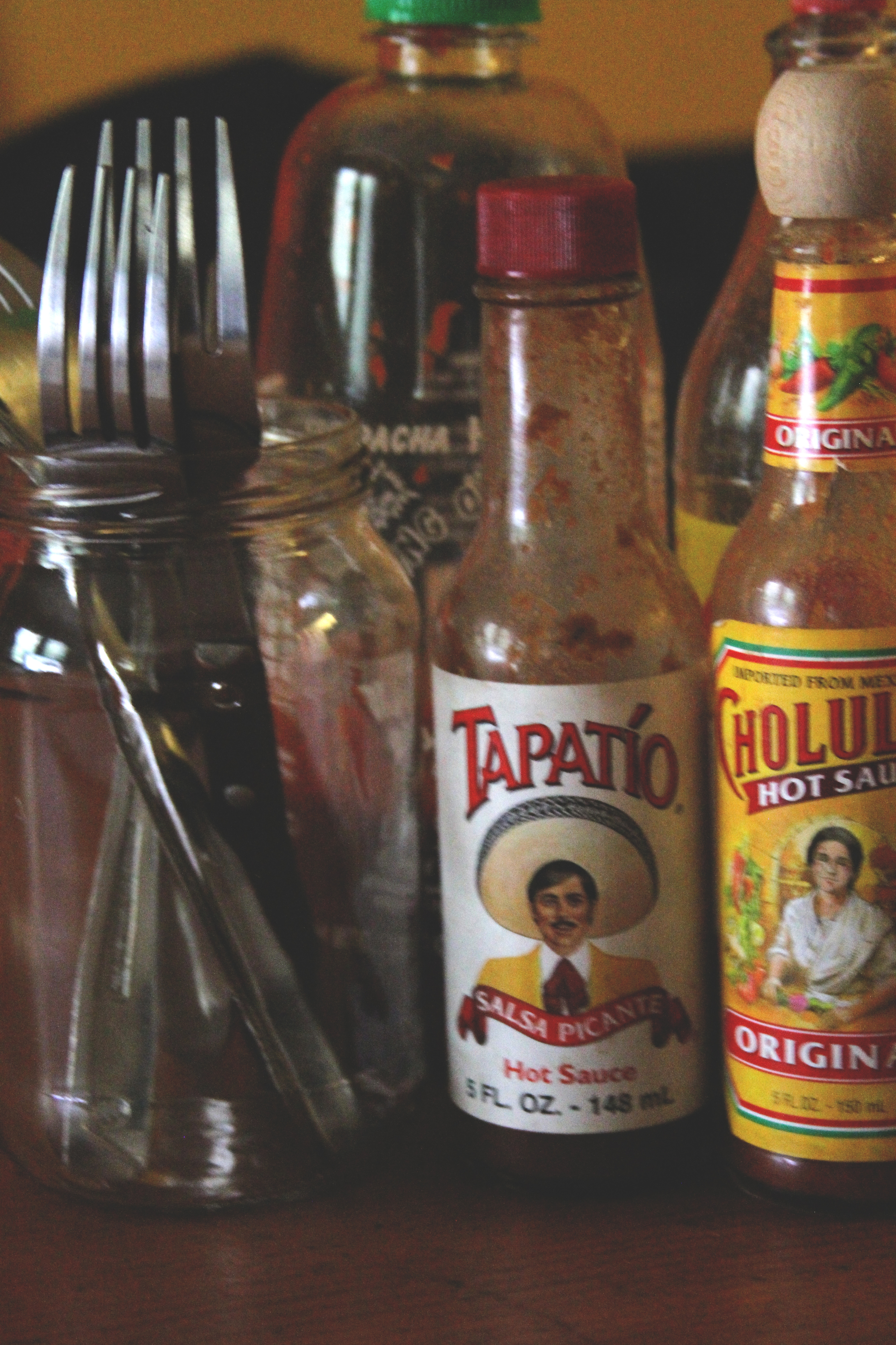 For this photo, I captured the most used items in my house: utensils and hot sauce. This says a lot about the style in which my housemates and i love to consume our food—spicy with a kick of flavor. I took a shot here at object framing and the light is casting an attached shadow on the objects.