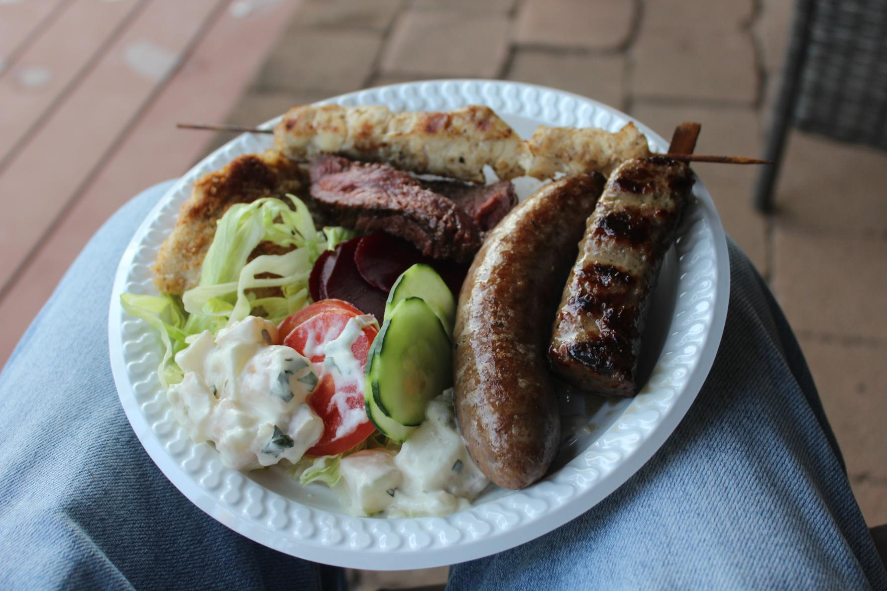 At this this barbecue there is crocodile meat, kangaroo meat, emu meat, camel sausage, goat meat and some vegetables.