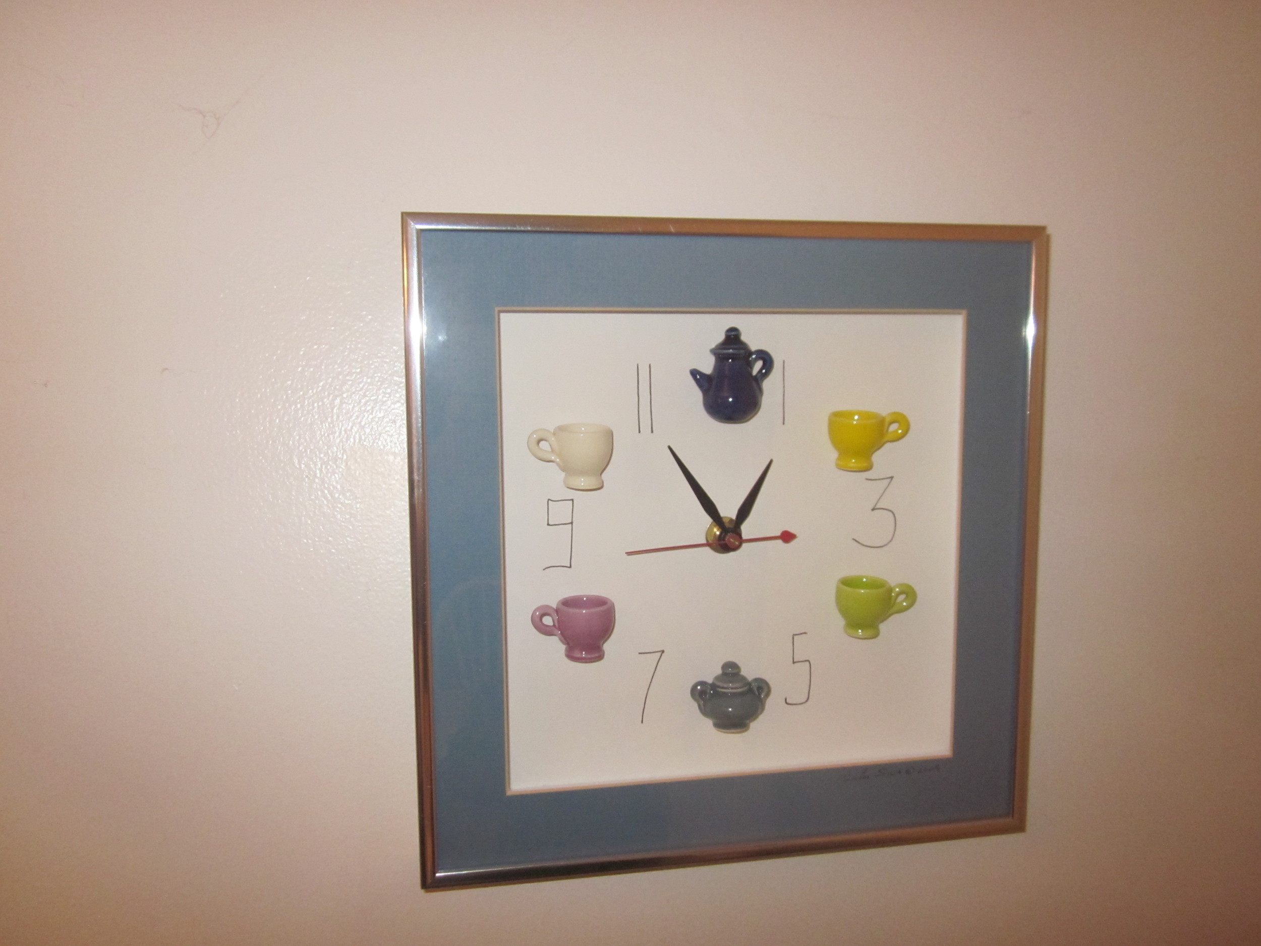 """COFFEE TIME OUT This whimsical clock cheers me up every time I look at it on my kitchen wall. It features unique, miniature hand-made mugs, sugar bowl and cream pitcher, and was created by Carlos Silva of Centuries Claywork who """"creates big moments with little pieces of art,"""" according to the company's website."""