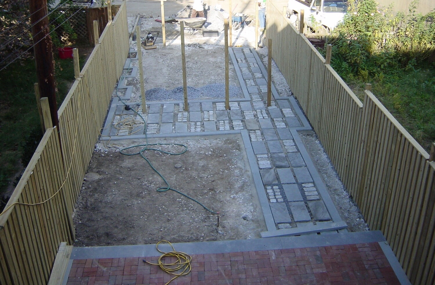 Hardscape elements of the garden begin to take shape : the new fence, the bluestone-and-granite path that leads to the driveway-to-be, and the raised brick terrace for entertaining. ©2018 Twelve gardens ltd.