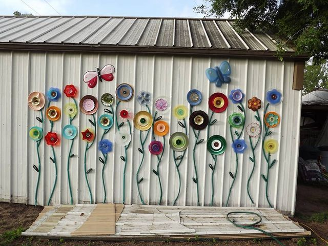 Brighten an old shed with colorful flowers made from plates and garden hose stems
