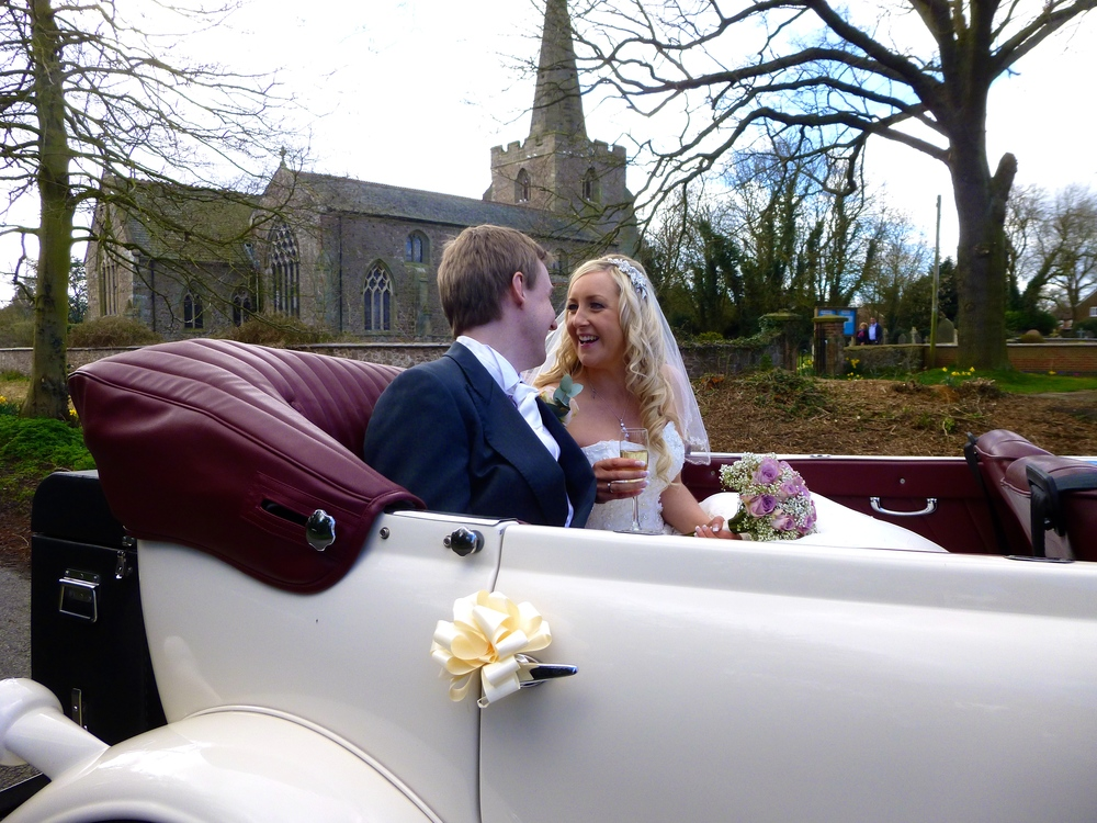 Bride and Groom, James and Dianne enjoy a champagne toast outside St. Mary's Church, Broughton Astley. The couple enjoyed a few minutes alone in The Beauford Tourer.