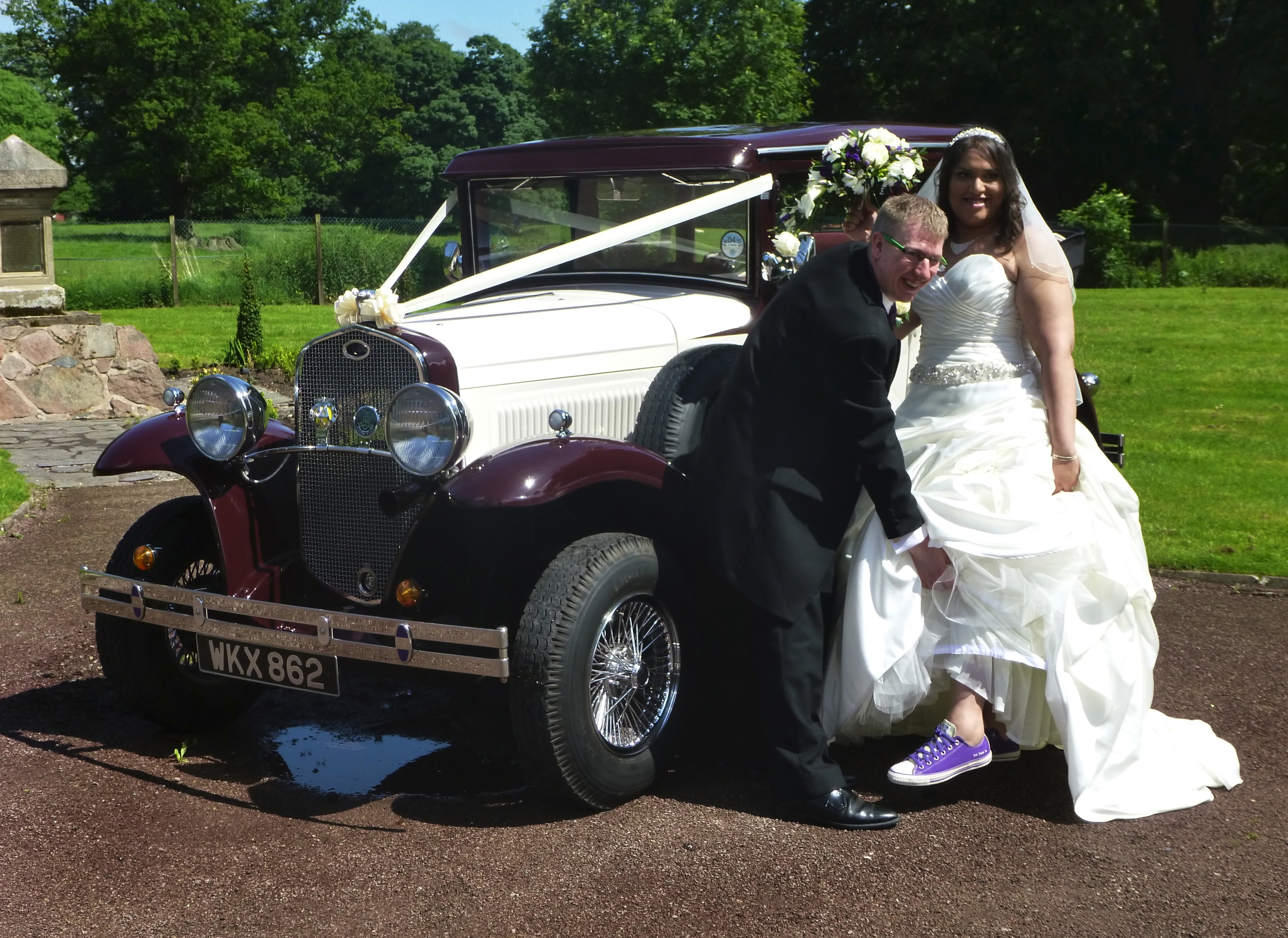 """Louise & Martin enjoying their """"fun"""" wedding. We get to see many different versions of footwear as the Bride exits the car. Louise was proud to display her comfortable trainers - matching the bridesmaids dresses. The puddle under the car is not a leak. The remains of the mornings downpour!"""