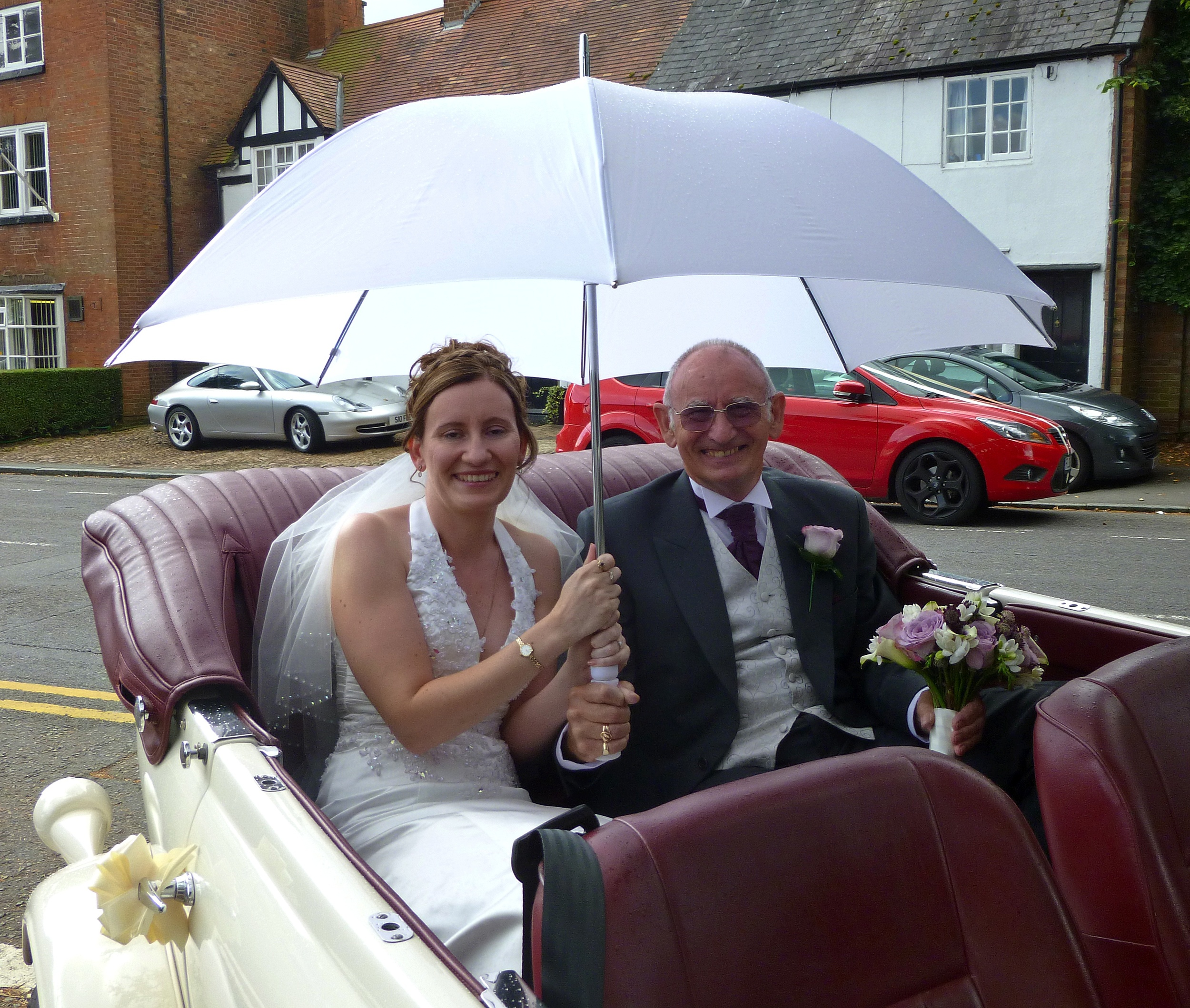 """Sharon and Father enjoying the umbrella """"fun"""" on arrival at St. Catherine's Church, Burbage for Sharon's marriage to Mark."""