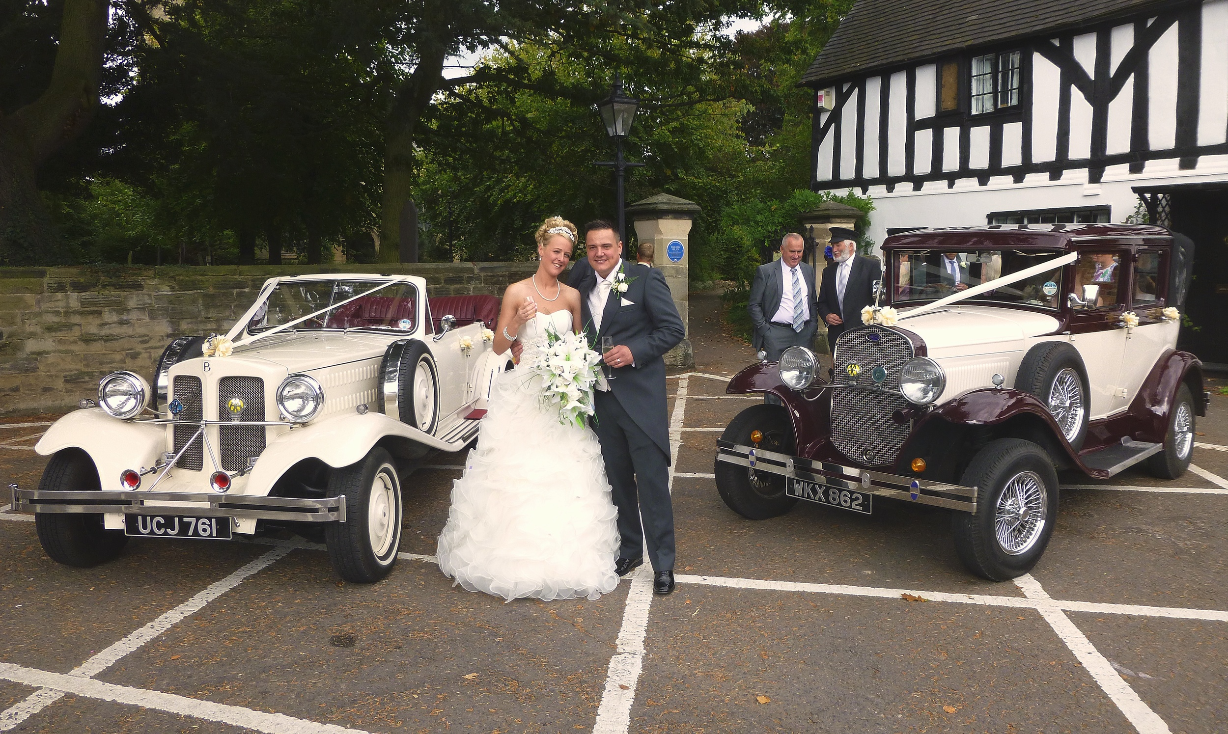 "Zoe and Steven happily posing for photos prior to taking the drive to the reception in Sutton Cheney. The large Yew tree to the extreme left of the photo has come to the end of being able to safely remain at the corner of the churchyard and is to be taken down. I think some brides may be quite pleased as the dead ""needles"" take some time to remove from the intricacies of the wedding gown!"