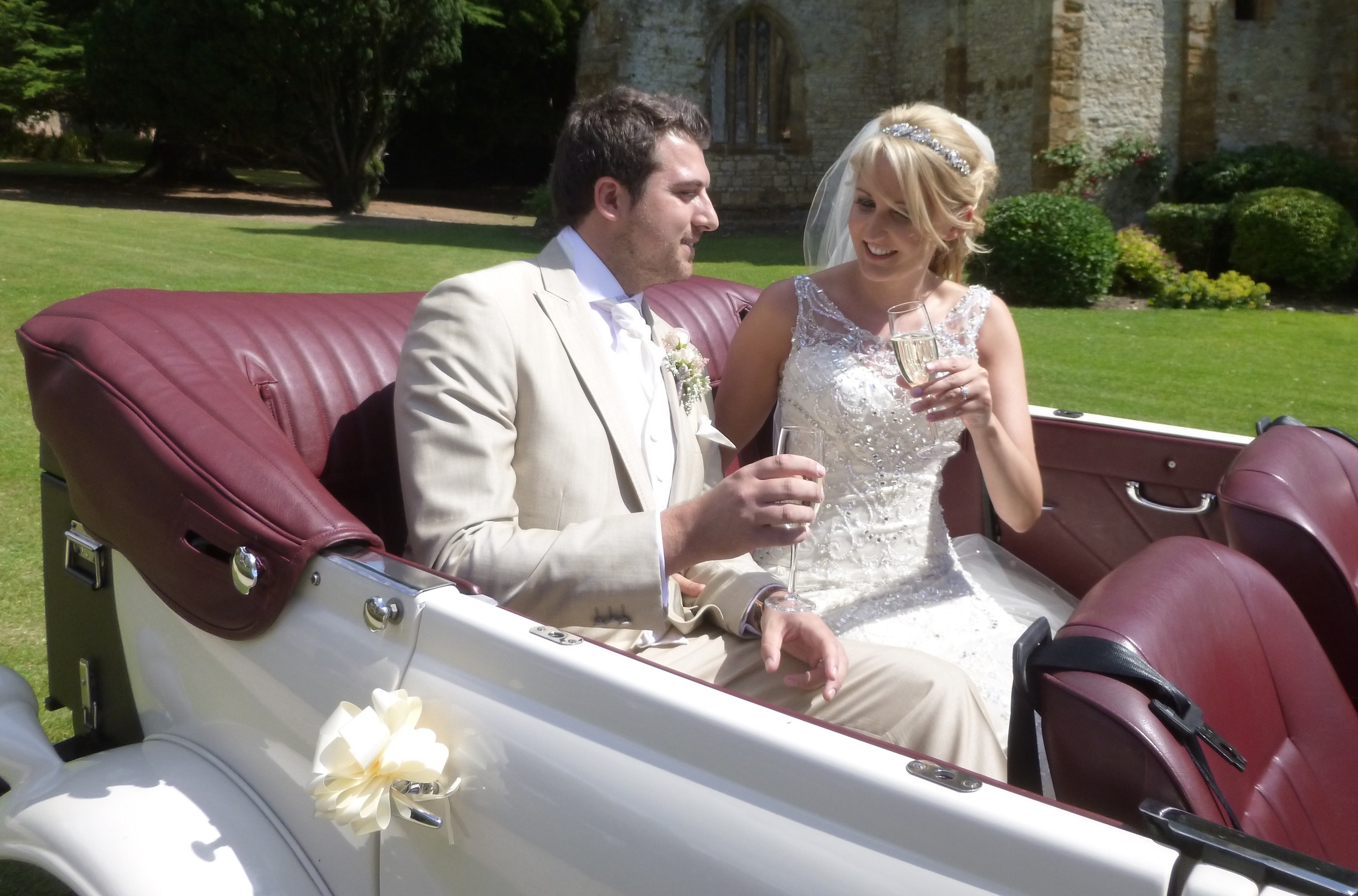 Sam and David enjoying a champagne toast, about to take slow drive in the lovely Warwickshire countryside that surrounds  Ettington Park . A magical way to start married life together.