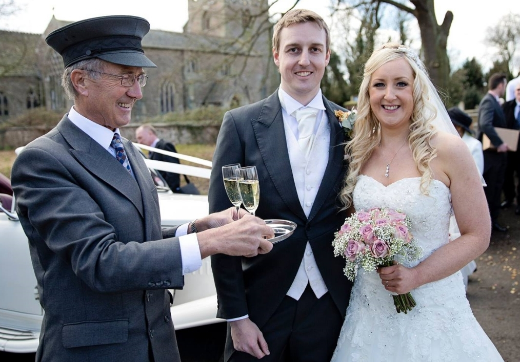 John Binns offering a champagne toast to the Bride and Groom as they leave St Mary's Church, Broughton Astley for a reception at Ettington Park Hotel in Warwickshire.