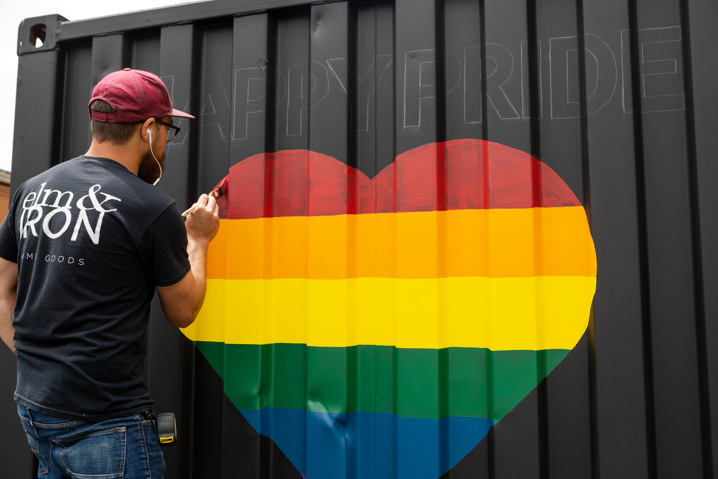 """Tony, painting """"Happy Pride"""" on one of our elm & IRON trailers."""