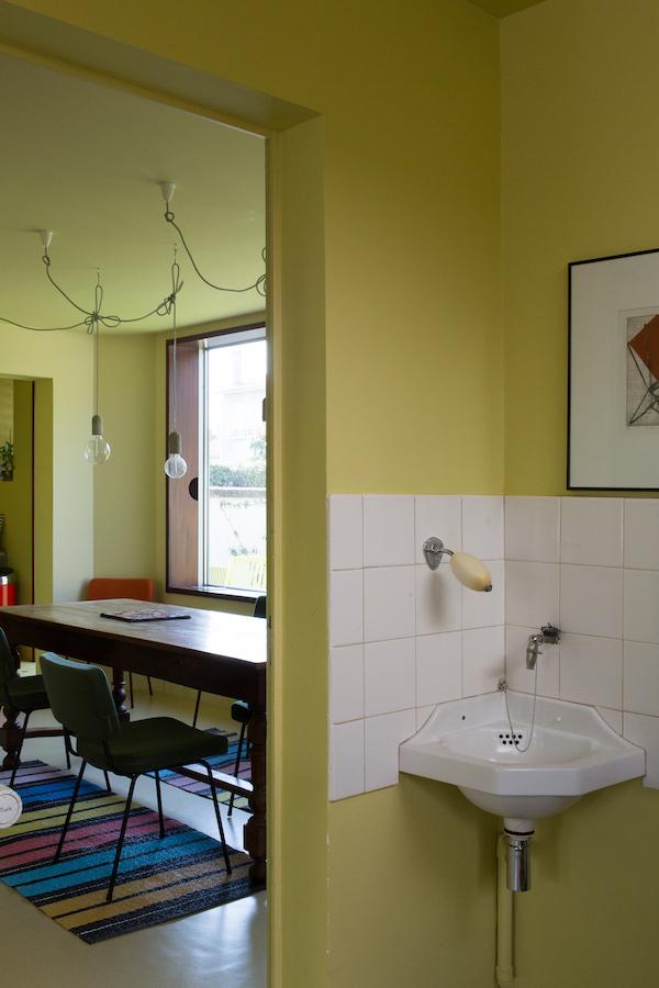 Comment rénover sans nostalgie ?   La maison 50 est située dans le centre de Royan, ville bombardée massivement pendant la seconde guerre mondiale, et reconstruite entre 1947 et 1965. La maison, construite par l'architecte parisien Richard Prince en 1952 , est l'ancien syndicat des gens de mer. L'édifice dispose d'un bureau au rez-de-chaussée et d'un logement de fonction à l'étage. Le bâtiment est totalement orienté sur la rue, au nord.  Le projet propose deux interventions : il ouvre la maison sur le jardin, et crée une porosité transversale. Les pièces d'origines sont conservées dans leur forme originelle, le programme s'adapte. L'intention architecturale du projet initial est conservée, mais la rénovation rectifie certains inachèvements. Un travail précis de préservation / remplacement / création est mené. Les portes intérieures, les poignées, les menuiseries extérieures sont nettoyées et réparées. Les menuiseries en niangion au mécanisme d'époque sont révisées. De nouveaux volets en pin d'orégon sont fabriqués. Les sols existants sont tous conservés, avec l'ajout de «rustines» aux endroits où le sol est abîmé. Deux portes intérieures sont créées, pour compléter les porosités transversale et longitudinale du projet. Chaque pièce compte alors entre deux et trois portes ; la circulation dans la maison devient fluide.  Côté jardin, deux grandes baies en aluminium, fixées en applique, constituent la seule intervention actuelle. Le caractère exceptionnel des deux baies rend hommage à l'enthousiasme de la reconstruction, au goût du défi. Il prolonge l'histoire de la maison, et l'accroche au XIX ème siècle, sans nostalgie.  L'intérieur est abordé avec le même souhait. Pour résister à la tentation d'une approche décorative d'un esprit 50 revisité, la maison est conçue comme un monochrome jaune/vert. Trois nuances sont réparties en fonction de l'étage, du programme, et de l'orientation de la maison, selon une approche scientifique (optique) de la couleur. Toute référence 