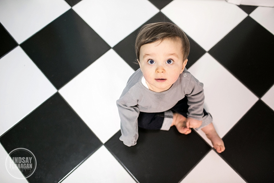 Baby Henry posing on a checkerboard floor