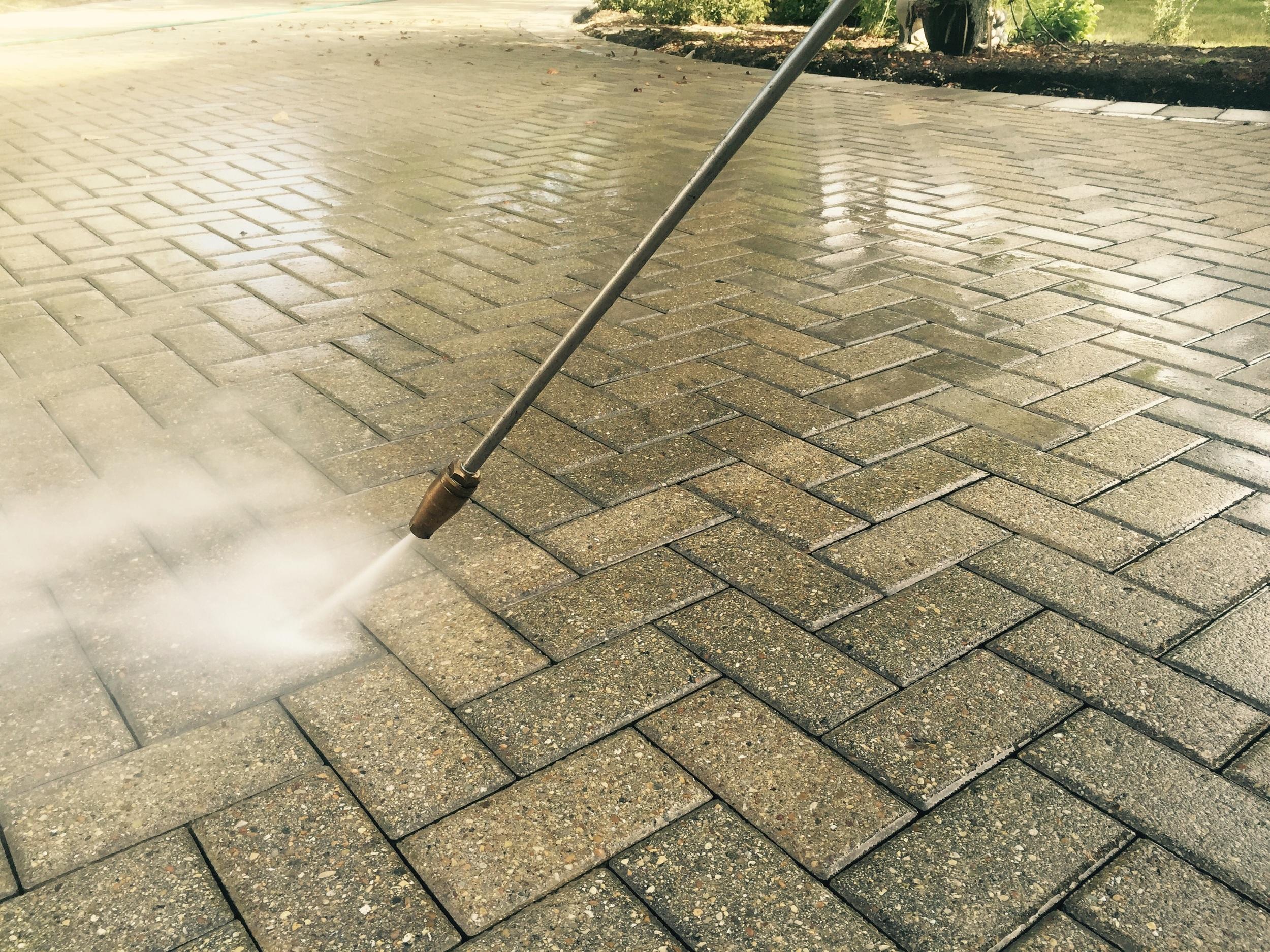 Pressure washing Unilock pavers.