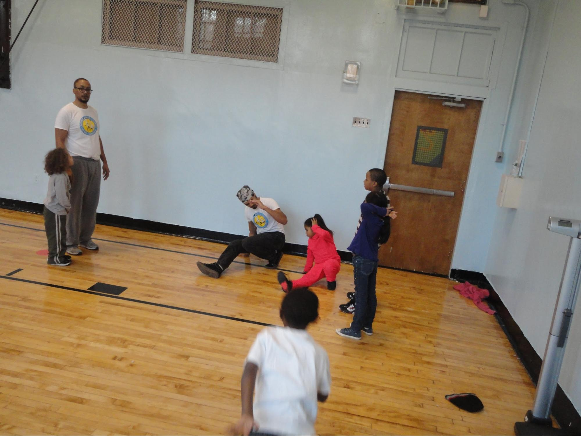 ABA teaching artist teaches role, a whole body roll important in capoeira floor movements.