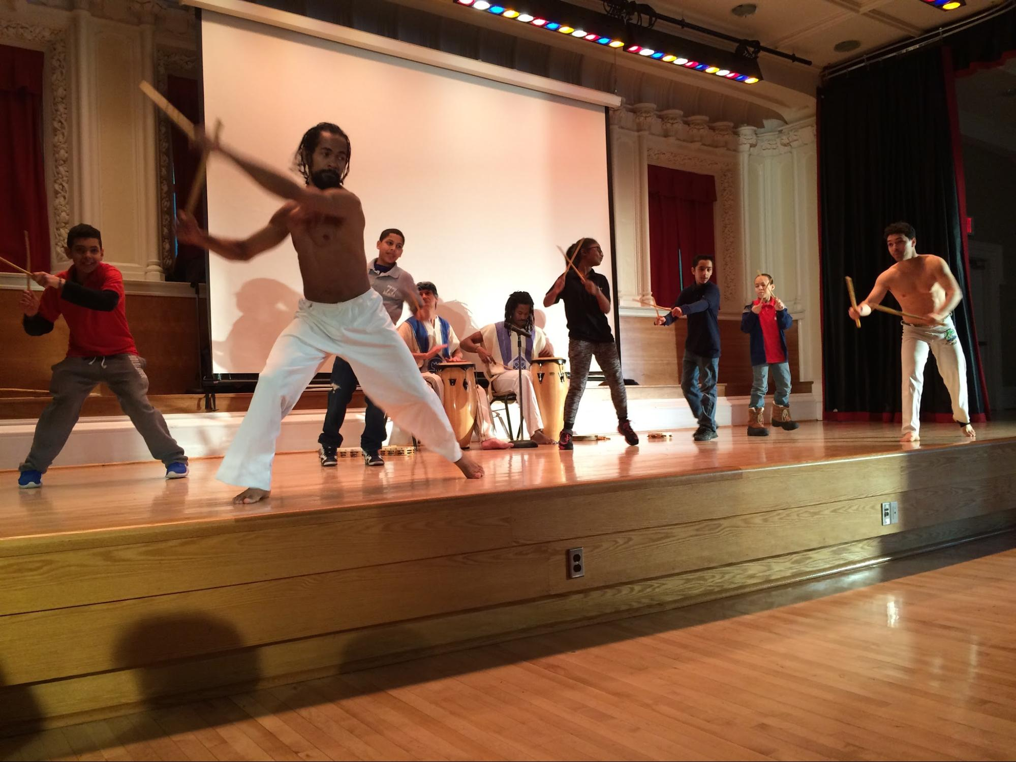 Capoeira performing artists with Afro Brazil Arts Troupe lead audience participation with Maculelê, a warrior dance from the sugar cane fields of Brazil, followed by first-time students from IS 77 in Queens, NY.
