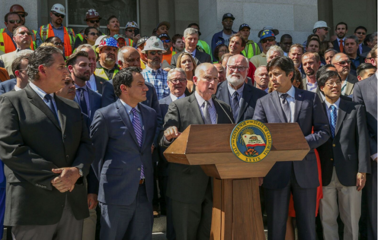 Gov. Brown announces California's infrastructure investment plan, flanked by leaders of the State Legislature and the hardhats that are actually ready to build something. Photo Source: governor.ca.gov.