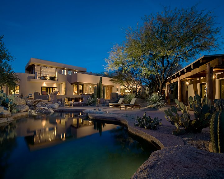 The addition of landscape lighting of this adobe inspired home in Arizonasubtly blends interior and exterior spaces, helping to eliminate the blackmirror effect where you see your own reflection instead of the viewbeyond. LED accent lights and decorativefixtures lamps with LED sourcesprovide dramatic illumination while saving moneyand maintenance.  Lighting Design- Randall Whitehead www.randallwhitehad.com   Interior Design- John Martin,  www.turnermartindesign.com   Photography-Jeff Zaruba  www.jeffzaruba.com