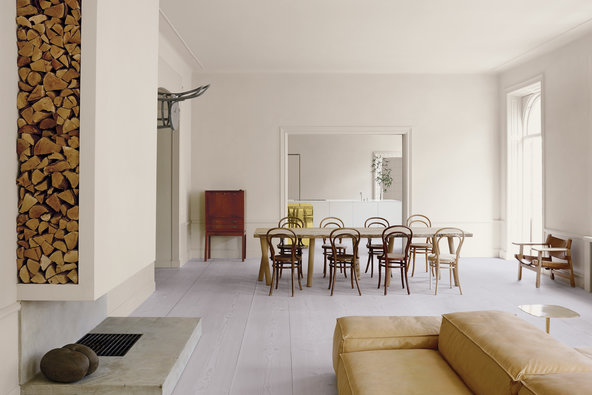 The living area is defined by a modular sofa by Piero Lissoni for Living Divani, a fireplace and a dining table conceptualized by Italian-Austrian designer Matteo Thun and manufactured by Riva 1920. The table is surrounded by antique Thonet chairs, and a chair-clock on the wall is by the Austrian artist Markus Hofer.   Credit Henry Bourne
