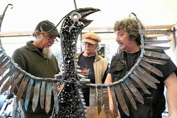 Obtainium Works' Shannon O-'Hare, left, helps Vallejo artist Jean Cherie, center, evaluate gun parts gathered from a recent gun buyback sponsored by the Robby Poblete Foundation. The artist is one of several chosen to create pieces of art for the foundation's Art of Peace project. The Phoenix in the photo is constructed by O'Hare using metal scrap from Obtainium and cartridge brass donated from local gun range. Photo: MIKE JORY/ROBBY POBLETE FOUNDATION