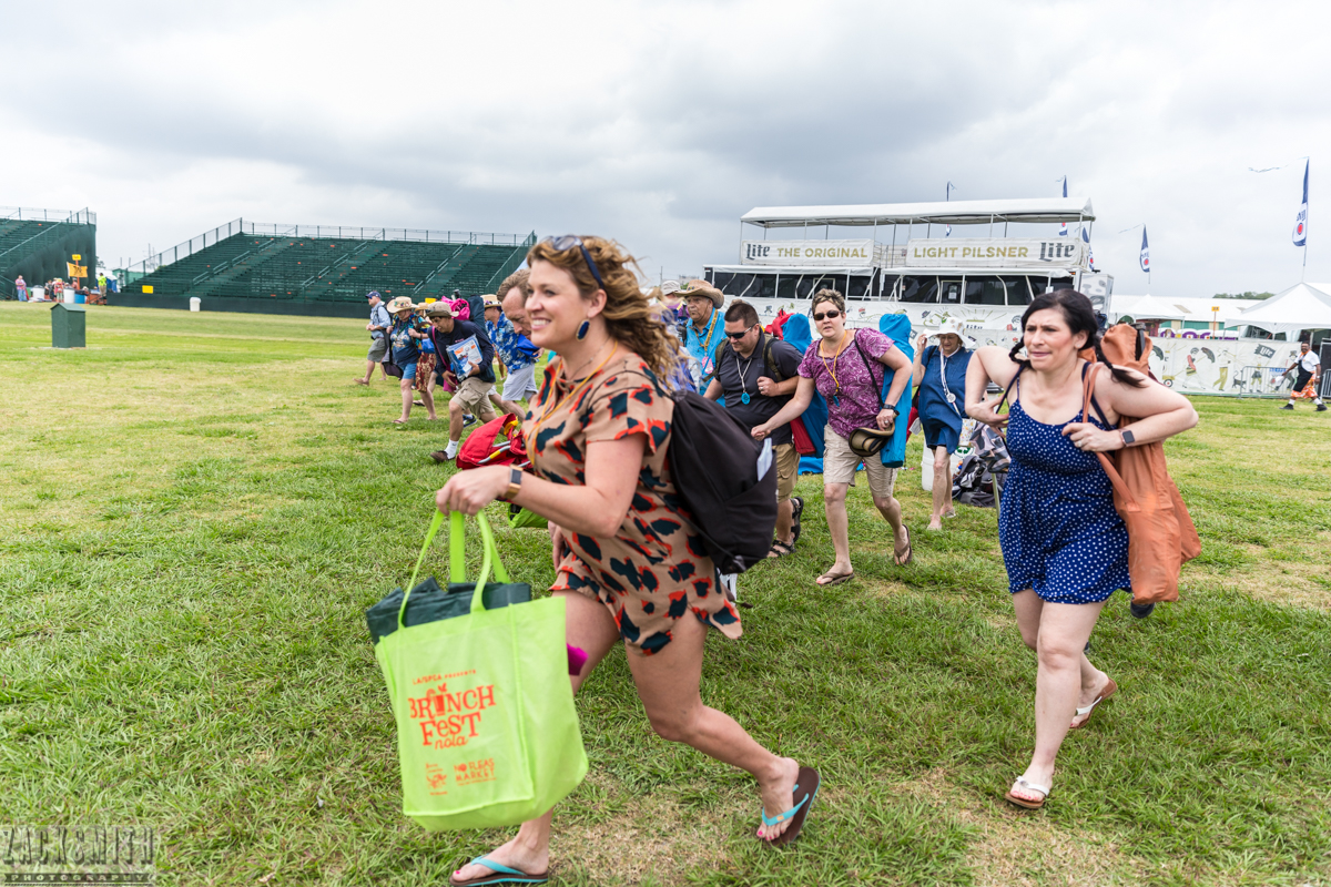 At the ceremonial sound of the bell, the Fairgrounds opens at the New Orleans Jazz and Heritage Festival as crowds race to claim their coveted spot on the lawn.