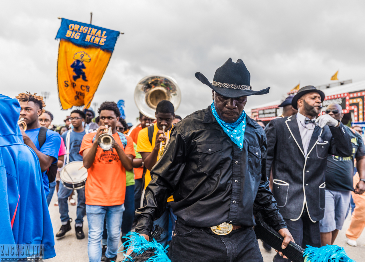 The Original Big 9 Social Aid and Pleasure Club march with The Chosen Ones Brass Band through the pathways of Jazz Fest.