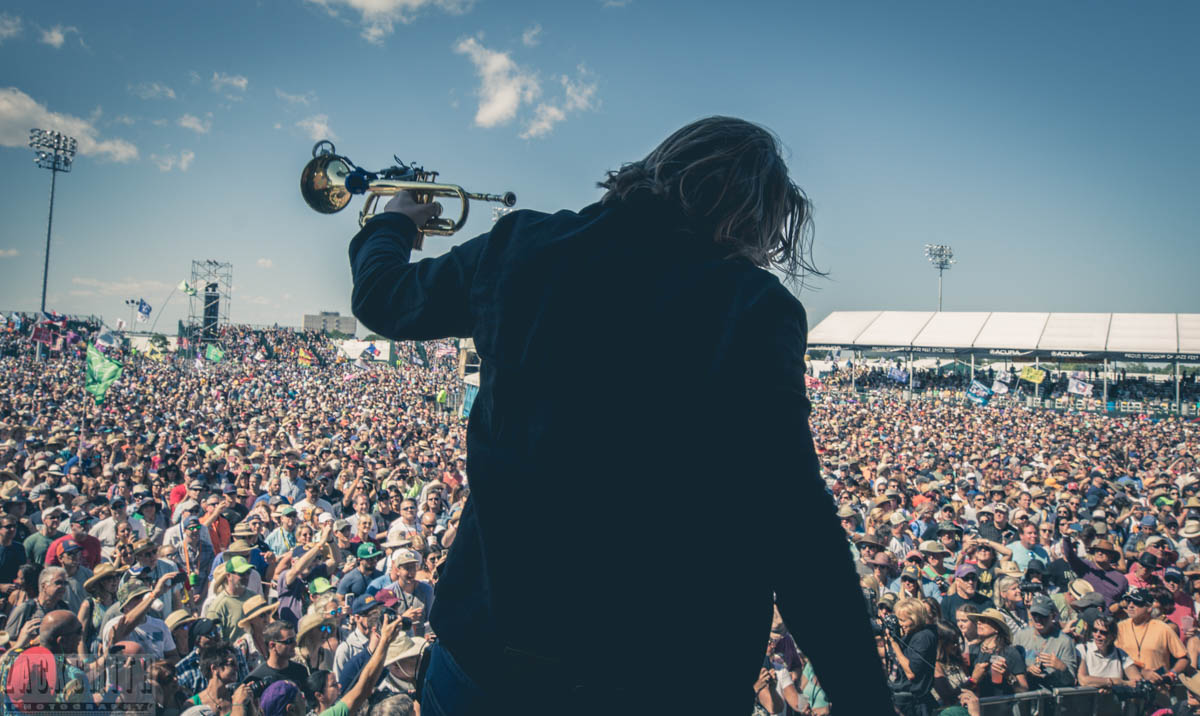 Trumpet and Keyboard player Michael Girardot performs over a sea of people at the Acura Stage of Jazz Fest 2017