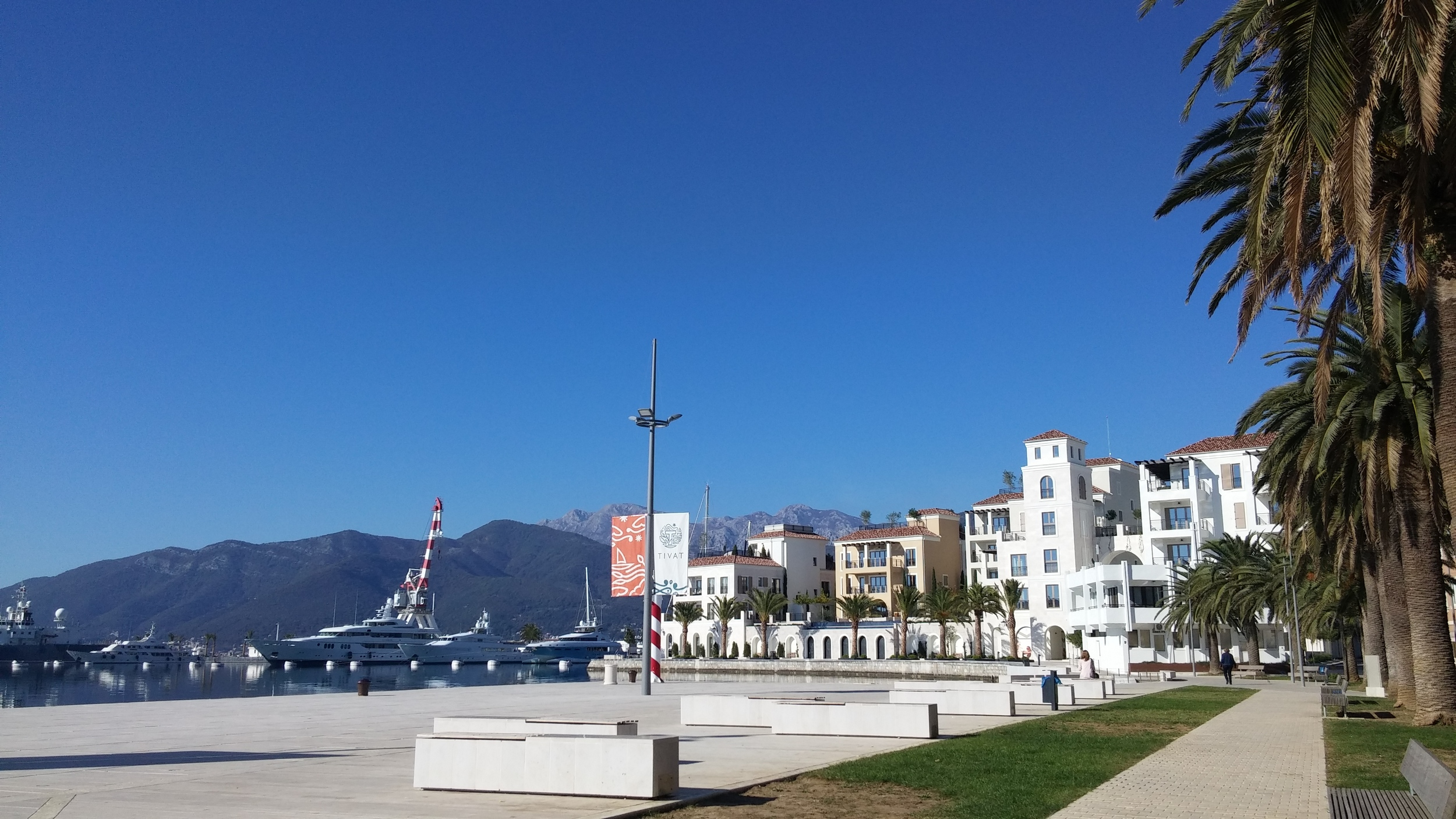 TIVAT , located in the central part of the Boka Kotorska Bay  Only a 15 minutes ride from Kotor, Tivat is a cosy and pleasant place to visit. In Tivat there is a lot of interesting attractions to see, such as Renaissance Summer House Buca in the center of the city, Flower Island, or Plavi Horizonti beach. Have a cup of Espresso on Šetalište Pine and watch multi-million dollar yachts anchored in Porto Montenegro, the biggest, luxurious marina in Montenegro. If you want to cool off, take a walk through City Park and read a good book surrounded by tall trees.