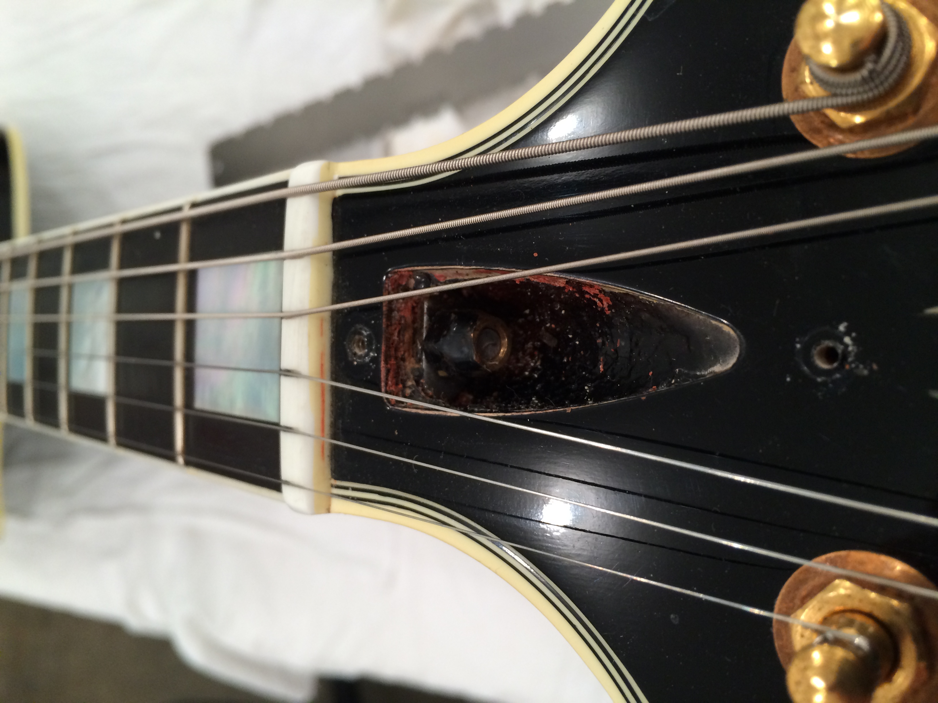 The truss rod nut exposed with all of the paint and finish junk covering the truss rod, washer and nut.
