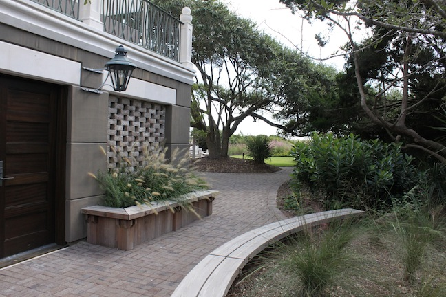 Ipe benches serve as short retaining walls; a wind-sculpted live oak tree is central elements of rear garden area.