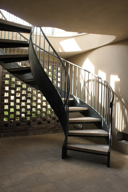 Bronze stair leads to the pool level; Ramon Grey stone tread and floor material, Savannah Grey brick lattice, beyond.
