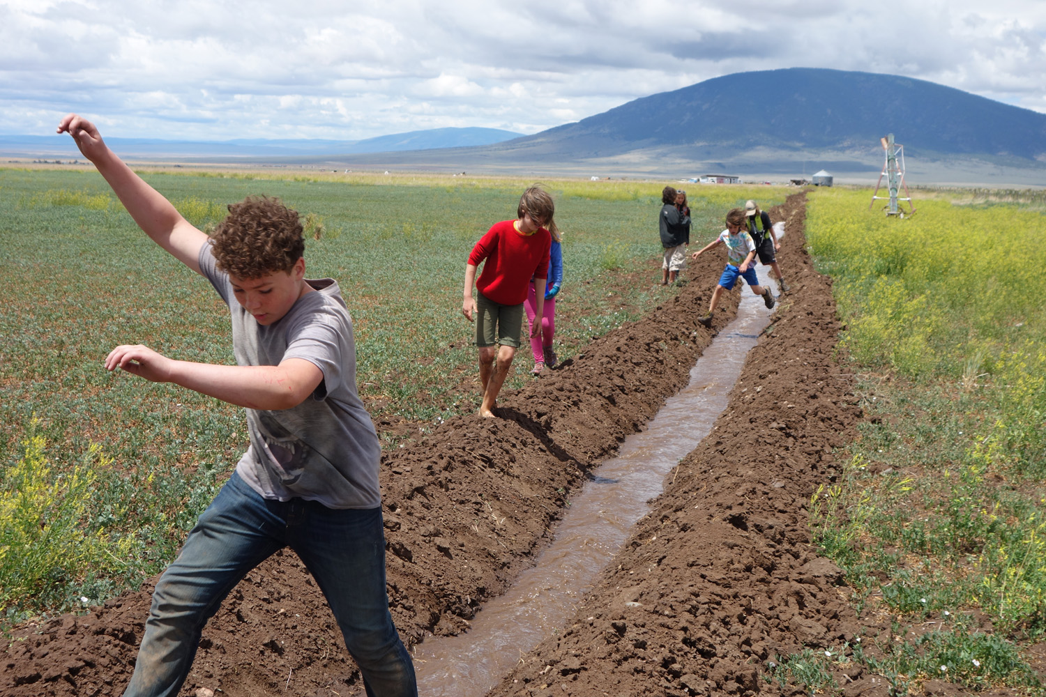 Summer campers from Sangre de Cristo Youth Ranch jump with joy at the first flood flow on Costilla Farm
