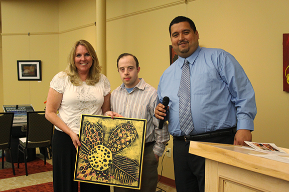 Self-Advocacy Committee President Victor Colon (far right) presents Joan Volpe with a painting by Artist Ross Carangelo,