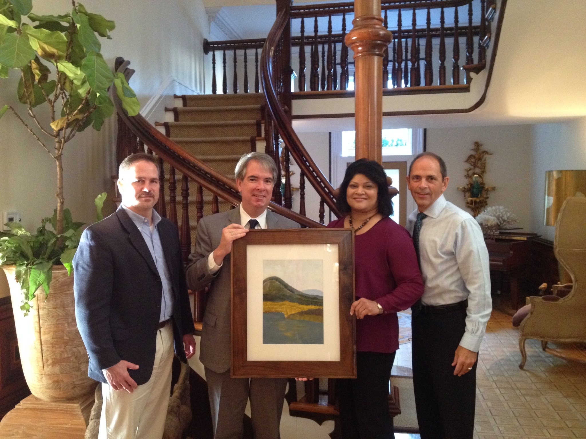 Lexington Deputy Executive Director Dan Richardson, Executive Director Shaloni Winston and Lexington Foundation Executive Director Wally Hart present SCAD Executive Director of External Relations Danny Filson with a painting of the Adirondacks. The piece was painted by Victor Colon who studies in Lexington's Creative Expressions Program and the frame was custom made by Susy Easterly, a local artist and SCAD graduate.