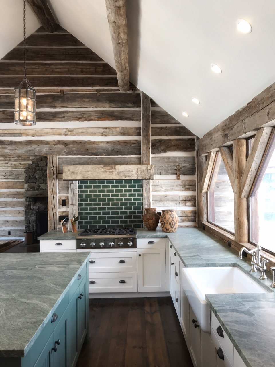 The full kitchen complete with rustic timbers and green granite countertops.
