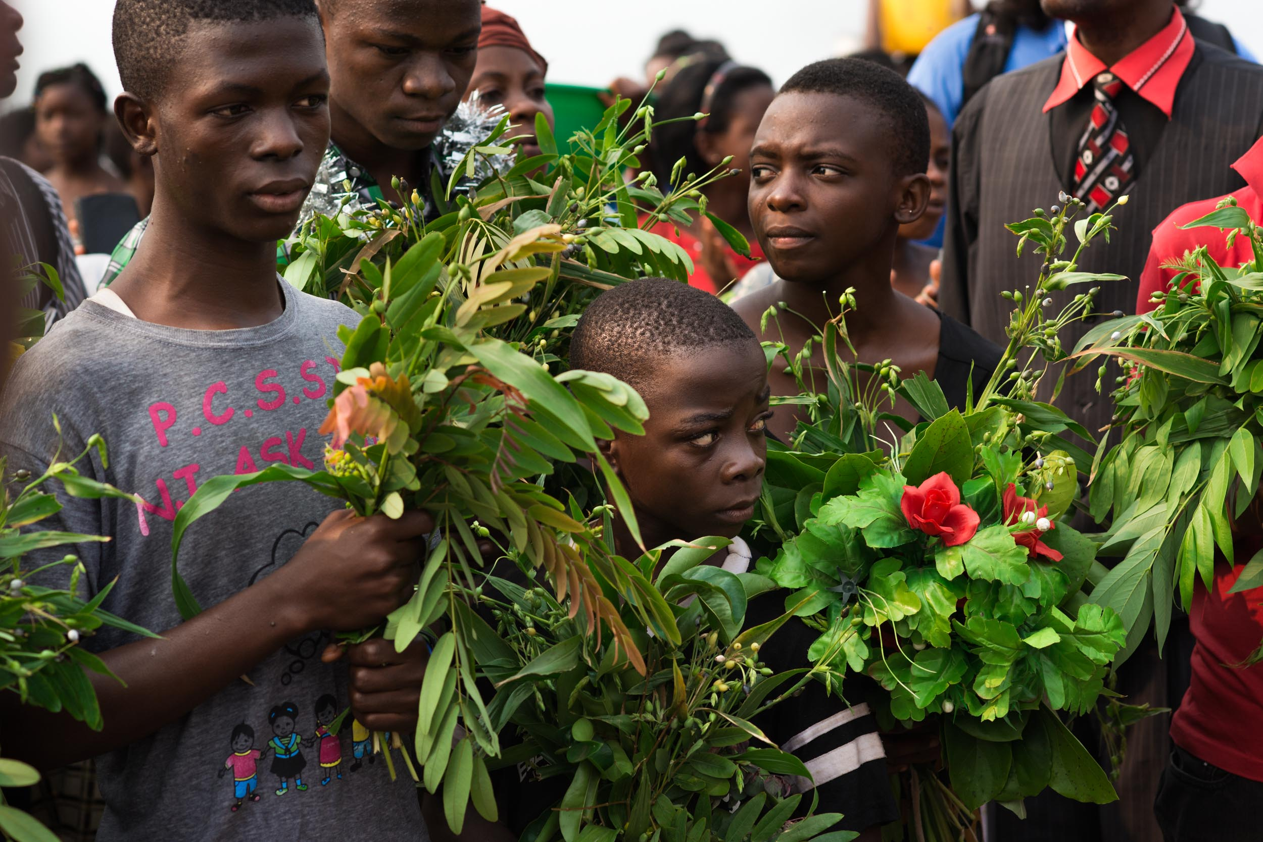 Hariza Kidoge (center) stands hidden among bouquets of local plants on the shore of Lake Tanganyika. On this day, he and five other orphans were baptized in the early morning by their faith leaders.