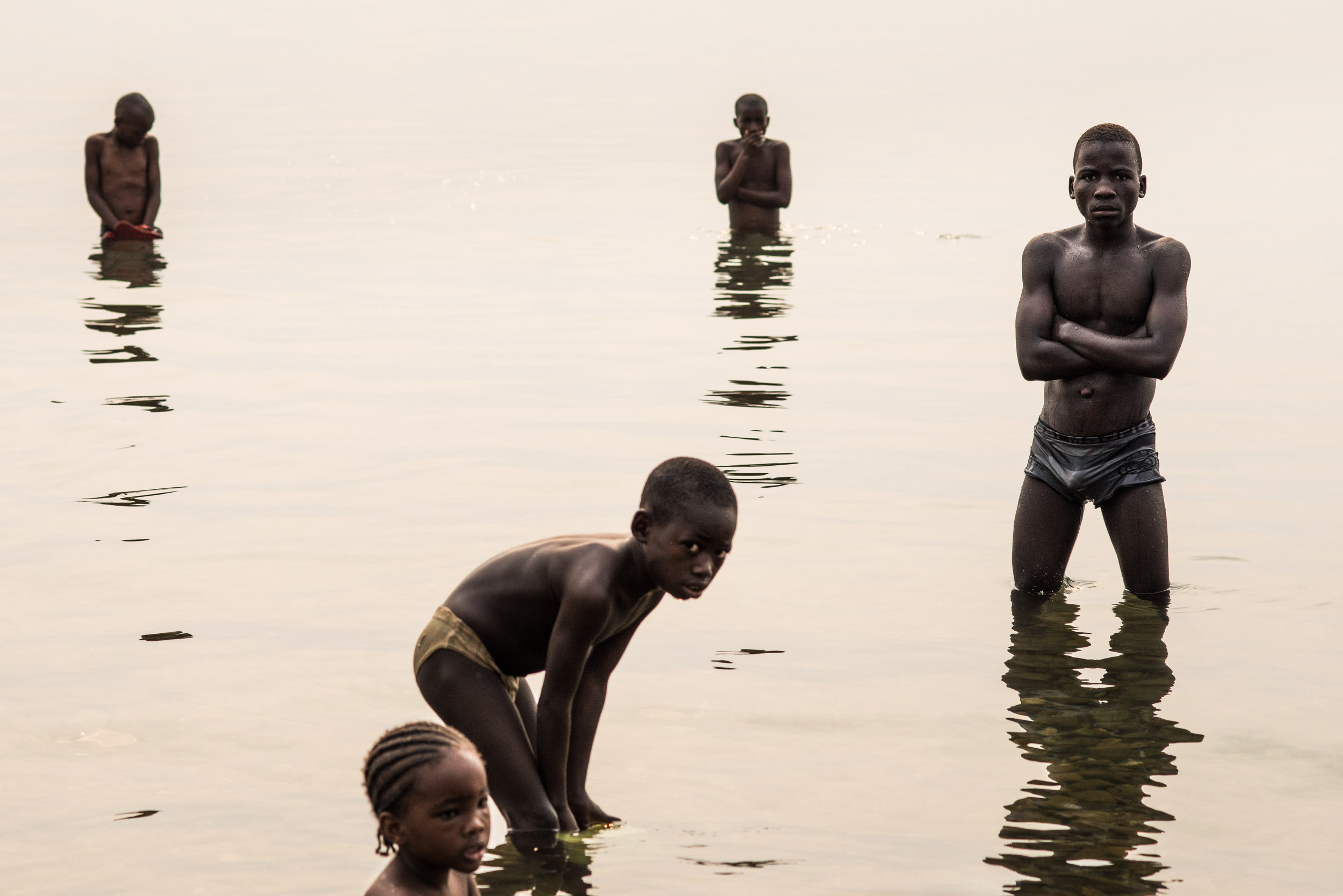 Residents of Uvira bathing near the CCMC in Lake Tanganyika in the dusty gray of a hazy sunrise on a Sunday Morning. Because of donor support, the orphans have access to more services and resources compared to most children outside of the CCC. There are times that it becomes a tension point with the community.