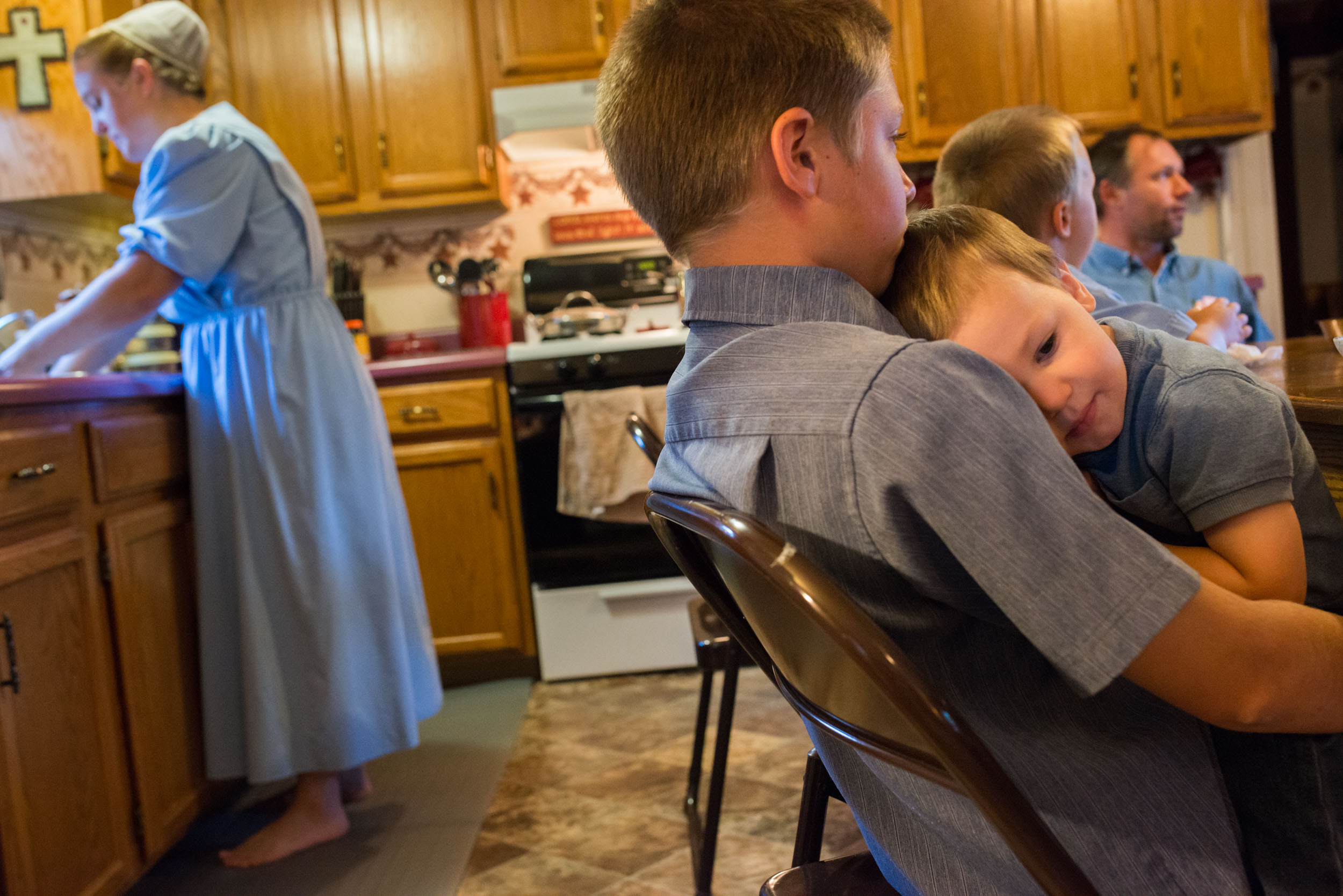 Austin Mast, embraces his brother Colton Mast, at the breakfast table before departing for school. Austin and two other siblings attend a private Mennonite school, while the youngest two children remain at home with Ruthann.