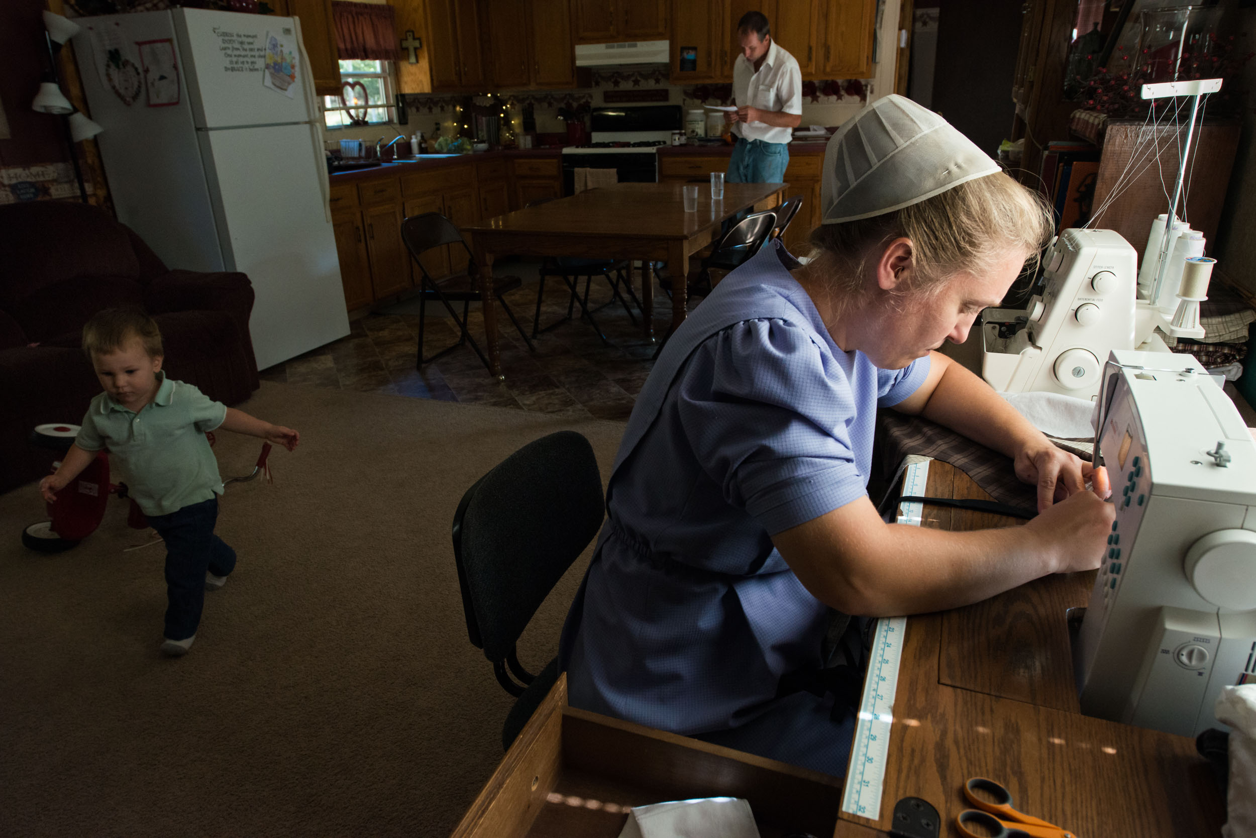 Ruthann sews after lunch while Nathan reviews mail before heading back to his outdoor responsibilities. The Masts had their current pre-fabricated home transported to a new location on the farm in July to make room for the new home construction.