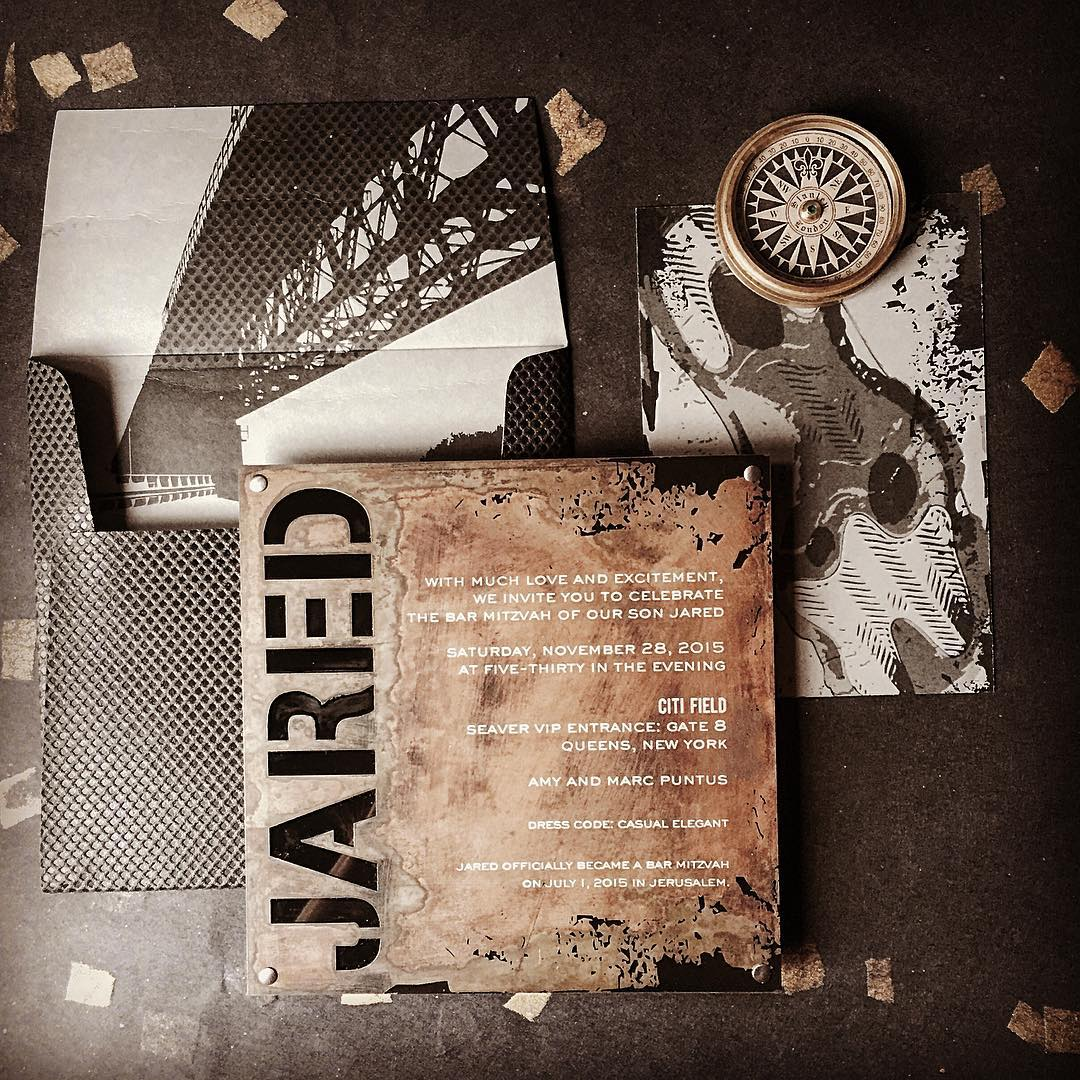 JARED BAR MITZVAH Oxidized steel invitation mounted to black acrylic with silver and black screen printing and nail studded corners. Seen with a custom pocked vinyl envelope and digitally printed bridge and sneaker motif.  Photograph by Suzie McKig