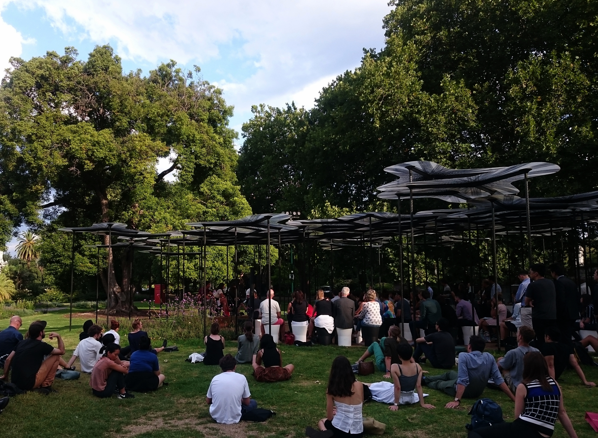 People listening to the panel discussion underneath and beside the MPavilion 2015,designed by  AL_A , studio of Amanda Levete.