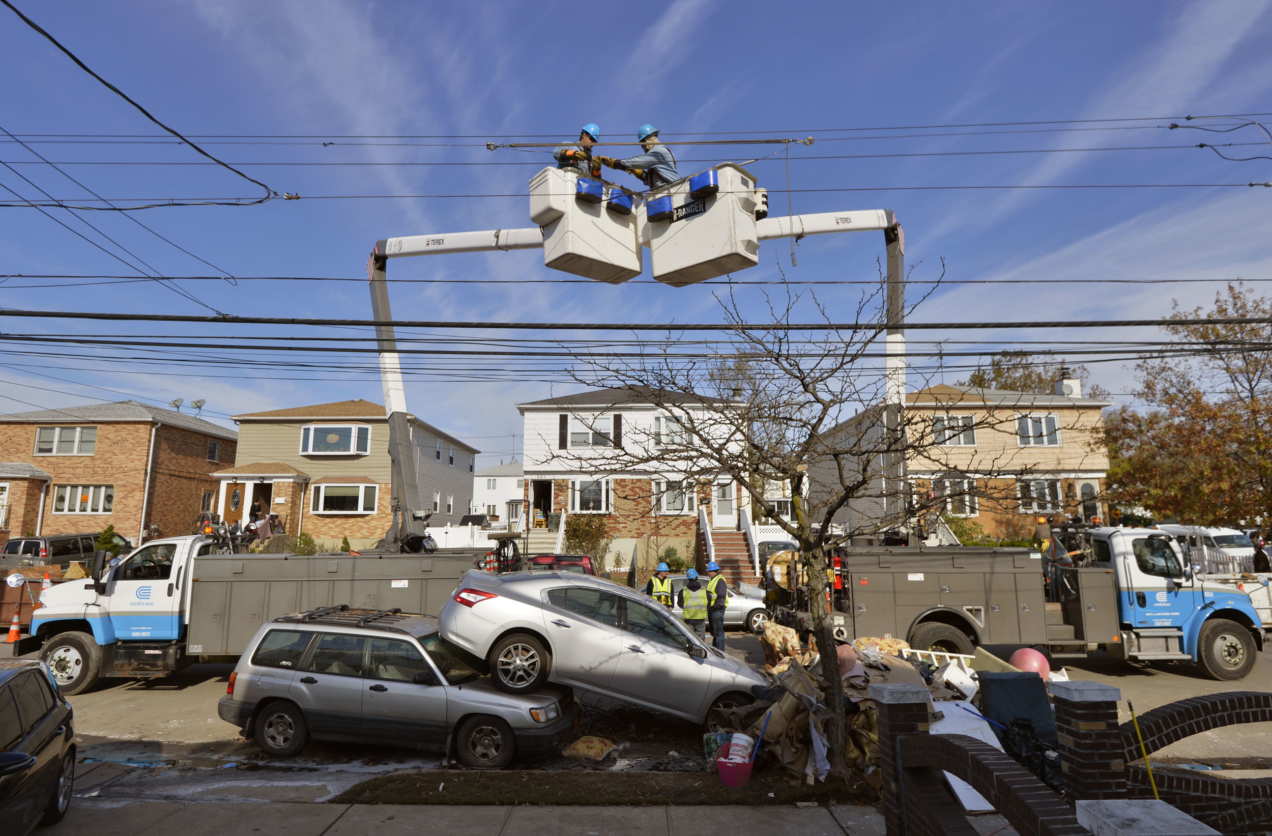 Crews from ConEdison reattach power lines over the two stacked cars as they restore power in store ravanged Staten Island.