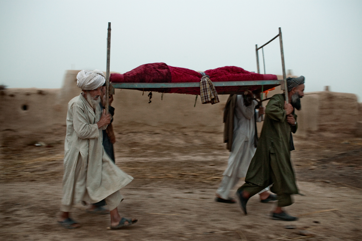 Family members of Gulmakay, a fourteen-year old Afghan girl killed by a U.S. Marines mortar strike, carry her body after presenting it to Marines in Abdullah Jan Village, Marja District, Helmand Province, Afghanistan.