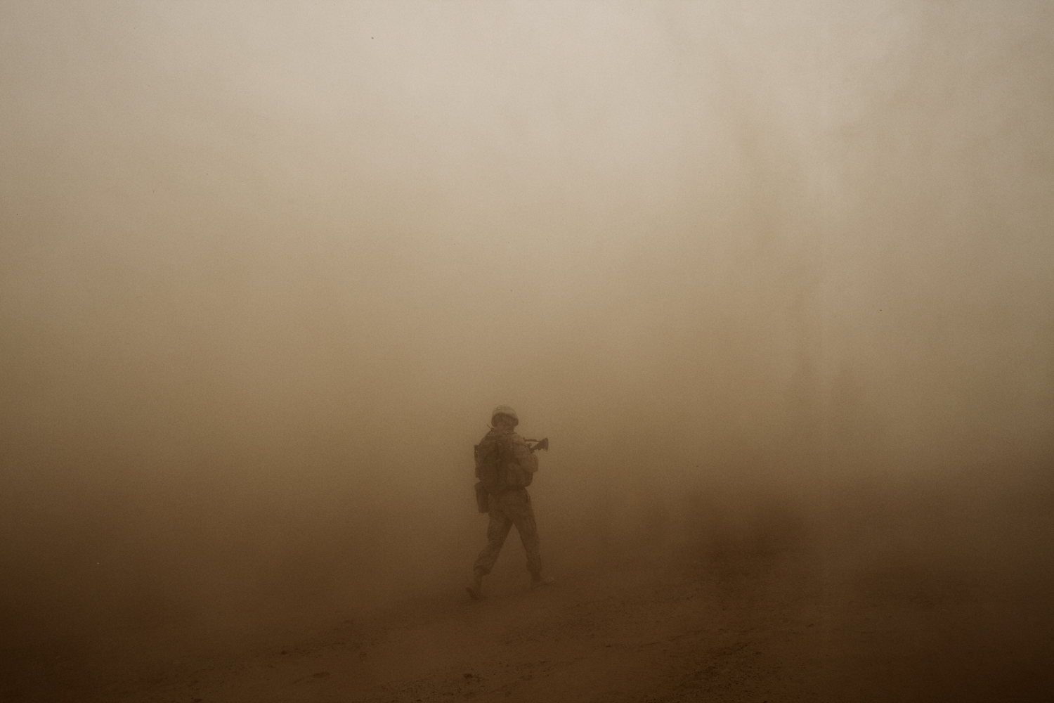 A U.S. Marine walks in the dusty rotor wash of a helicopter in Marja District, Helmand Province, Afghanistan.