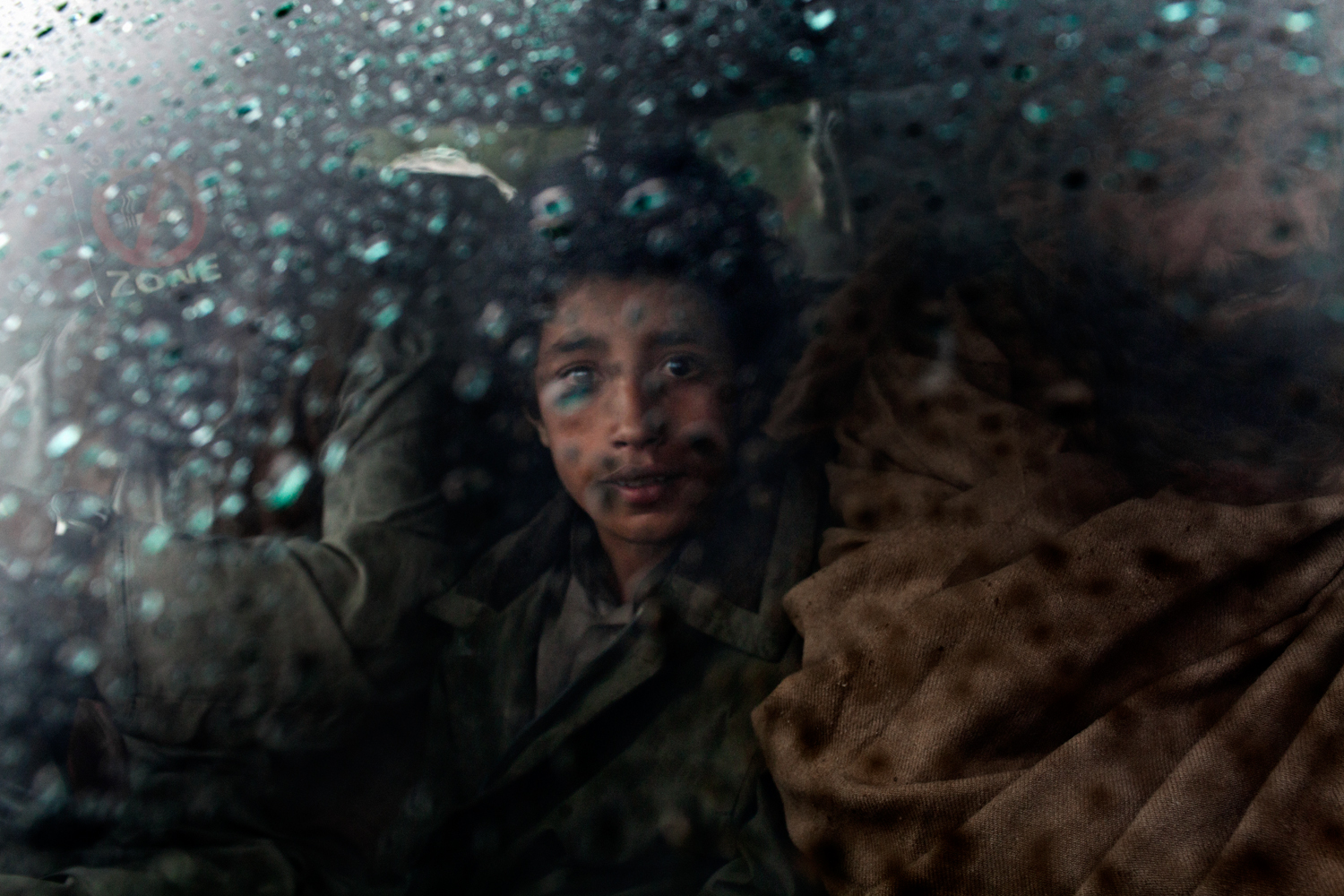 An Afghan boy at a checkpoint in the Korengal Valley, Kunar Province, Afghanistan.